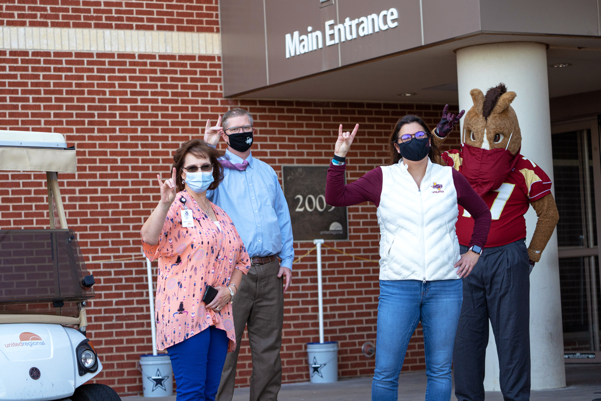 Kim Maddin, left, of United Regional accepted the donation of masks from Dr. David Carlston, Reagan Foster, and Maverick.